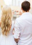 Los pares románticos en la ciudad que hace el corazón forman Foto de archivo libre de regalías