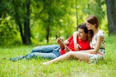 Los pares románticos hermosos con PC de la tableta en el verano ponen verde el parque Imágenes de archivo libres de regalías