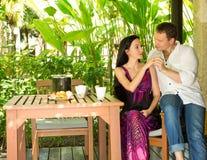 Los pares románticos jovenes felices que se sientan en una tabla y almuerzan en Imagenes de archivo