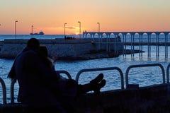 Los pares románticos miran la puesta del sol juntos por una tarde del invierno Fotos de archivo libres de regalías