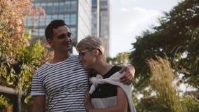 Los pares románticos multiétnicos jovenes sonrientes felices de la cámara lenta caminan juntos deteniéndose en un parque de la ci almacen de metraje de vídeo