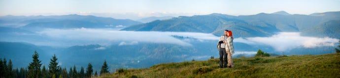 Los pares románticos que disfrutan de una mañana haze sobre las montañas Foto de archivo