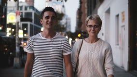 Los pares románticos sonrientes felices llevan a cabo las manos y hablan mientras que caminan a lo largo de igualar Soho, Nueva Y almacen de video