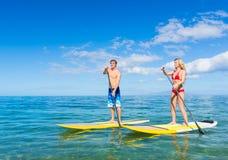Los pares se levantan la paleta que practica surf en Hawaii foto de archivo libre de regalías