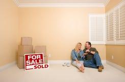 Los pares se sientan cerca de los rectángulos y de las muestras vendidas de las propiedades inmobiliarias Foto de archivo libre de regalías