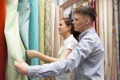 Los pares seleccionan las muestras coloridas de la cortina que cuelgan en tienda imágenes de archivo libres de regalías