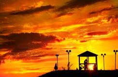 Los pares siluetean en la puesta del sol imagenes de archivo