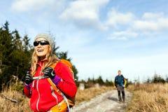 Los pares sirven y mujer que recorre en montañas Foto de archivo libre de regalías