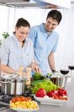 Los pares sonrientes beben el vino rojo que cocina en cocina Fotos de archivo