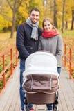 Los pares sonrientes con el cochecito de niño del bebé en otoño parquean Foto de archivo