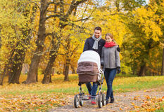 Los pares sonrientes con el cochecito de niño del bebé en otoño parquean Imagenes de archivo