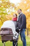 Los pares sonrientes con el cochecito de niño del bebé en otoño parquean Fotografía de archivo libre de regalías