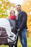 Los pares sonrientes con el cochecito de niño del bebé en otoño parquean Imagen de archivo libre de regalías