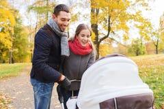 Los pares sonrientes con el cochecito de niño del bebé en otoño parquean Fotos de archivo