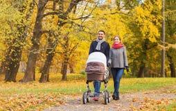 Los pares sonrientes con el cochecito de niño del bebé en otoño parquean Imagen de archivo