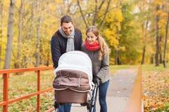 Los pares sonrientes con el cochecito de niño del bebé en otoño parquean Foto de archivo libre de regalías