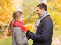 Los pares sonrientes con el manojo de hojas en otoño parquean Fotografía de archivo libre de regalías