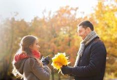Los pares sonrientes con el manojo de hojas en otoño parquean Imagen de archivo libre de regalías