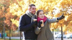 Los pares sonrientes con las tazas de café en otoño parquean almacen de metraje de vídeo