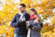 Los pares sonrientes con las tazas de café en otoño parquean Fotos de archivo libres de regalías