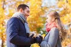 Los pares sonrientes con las tazas de café en otoño parquean Fotografía de archivo libre de regalías