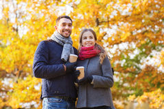 Los pares sonrientes con las tazas de café en otoño parquean Imágenes de archivo libres de regalías