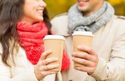 Los pares sonrientes con las tazas de café en otoño parquean Imagen de archivo