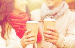 Los pares sonrientes con las tazas de café en otoño parquean Foto de archivo libre de regalías