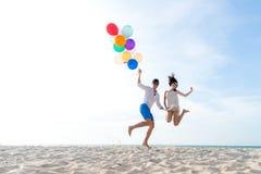 Los pares sonrientes dan mantener el globo y el salto unido en la playa El amante romántico y relaja luna de miel en vacaciones d fotos de archivo libres de regalías