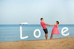 Los pares sonrientes felices con la inscripción aman en la playa Imagen de archivo libre de regalías