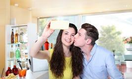 Los pares sonrientes hacen un selfie en barra Fotos de archivo
