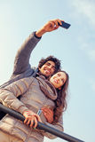Los pares sonrientes haciendo un selfie abrazado imágenes de archivo libres de regalías