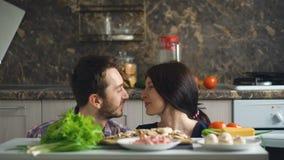 Los pares sonrientes hermosos juegan y se besan sobre la tabla con las verduras mientras que cocinan en cocina almacen de metraje de vídeo