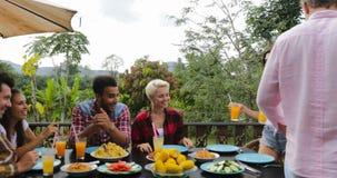 Los pares traen a la gente del jugo que pasa la comida que come en los amigos jovenes de la terraza que hablan sentarse en la com almacen de video