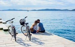 Los pares turísticos, el hombre y la mujer con las bicicletas en alto pavimentaron la acera de piedra cerca de la agua de mar el  fotografía de archivo libre de regalías