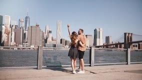 Los pares turísticos europeos felices se colocan de abrazo, arman aumentado disfrutando de la opinión épica de Manhattan en cámar almacen de video