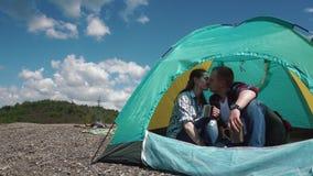 Los pares turísticos jovenes tienen un momento sensual en tienda verde clara El hombre joven y la mujer hermosos comparten besos  almacen de metraje de vídeo