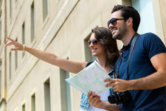 Los pares turísticos jovenes utilizan su mapa y señalar adonde quieren Imágenes de archivo libres de regalías