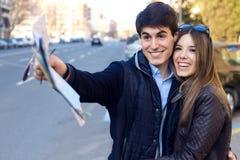 Los pares turísticos jovenes utilizan su mapa y señalar adonde quieren Foto de archivo