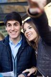 Los pares turísticos jovenes utilizan su mapa y señalar adonde quieren Fotografía de archivo