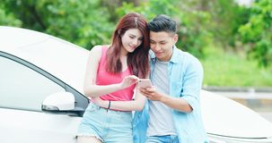 Los pares utilizan el teléfono con el coche imagenes de archivo