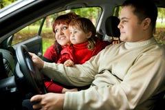 Los pares y la niña casados se sientan en coche en parque Fotos de archivo