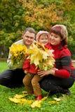 Los pares y la niña recogen las hojas de arce en parque Fotos de archivo libres de regalías