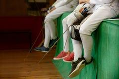 Los participantes de las muchachas en competencias de cercado en las espadas descansan entre las competencias Imágenes de archivo libres de regalías