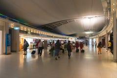 Los pasajeros caminan más allá de un área de compras en su manera a la salida Foto de archivo