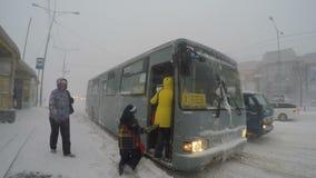 Los pasajeros con los niños entran en el autobús público en la parada de autobús durante ventisca pesada del invierno