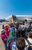 Los pasajeros consiguen a bordo del avión Imágenes de archivo libres de regalías