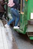 Los pasajeros consiguen en la tranvía en una parada imagen de archivo