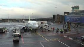 Los pasajeros dejan el avión, por otra parte descargan el equipaje metrajes