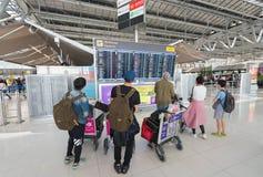 Los pasajeros del aire miran el calendario de salidas en el aeropuerto de Bangkok Fotos de archivo